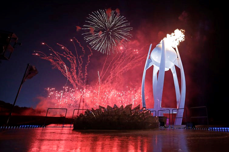 Fireworks explode behind the Olympic flame during the opening ceremony of the 2018 Winter Olympics in Pyeongchang, South Korea, (AP Photo/David J. Phillip,Pool)