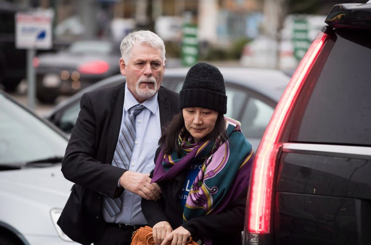 Huawei chief financial officer Meng Wanzhou, right, is escorted by a member of her private security detail while arriving at a parole office in Vancouver in December 2018.