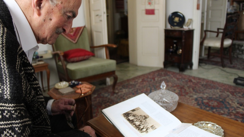 Teddy looks at photographs of his 1938-1939 class in the German Colony, which was near his home neighbourhoods of Talbiyeh and Katamon. [Mary Pelletier/Al Jazeera]