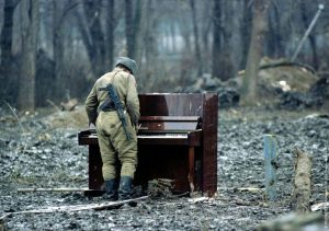 Soldier standing, playing abandonned piano